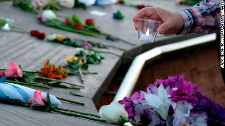 A visitor places a candle among flowers at the Columbine Memorial at Clement Park in Littleton, Colorado, during a community vigil for the 20th anniversary of the Columbine High School mass shooting on April 19, 2019. - 12 students and one teacher were massacred by two heavily armed students nearly 20 years ago during the Columbine High School shooting on April 20, 1999. (Photo by Jason Connolly / AFP) (Photo by JASON CONNOLLY/AFP via Getty Images)