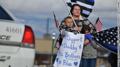 Vala Clark, center, with her grandchildren Wesley Haymore, 10, left, and his sister Andilyn, 7, waves flags for Officer Eric Talley in front of King Soopers on State Highway 7.