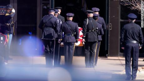 An honor guard carries the casket of fallen Boulder Officer Eric Talley.