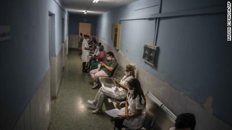 کیوبا کے شہر ہوانا میں 24 مارچ کو صحت کی دیکھ بھال کرنے والے کارکن دالان میں بیٹھے جب وہ سوبیرانا 02 کوویڈ 19 ویکسین کے ٹیکے لگائے جانے کا انتظار کرتے ہیں۔