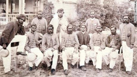A photo of the all-Aboriginal cricket team at the Melbourne Cricket Ground in 1866, with coach Tom Wills at the back in the center and Johnny Mullagh standing to his right. Yanggendyinanyuk is on the far right.