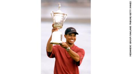 Woods holds up the US Open trophy.