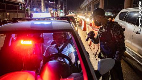 A police officer inspects motorists at a quarantine checkpoint on March 29, 2021 in Marikina, Metro Manila, Philippines.