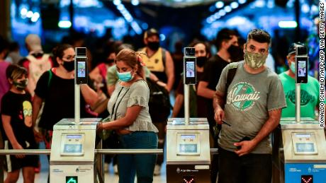 People wearing protective face masks enter to the Constitucion train station in Buenos Aires, on April 6, 2021. - Covid-19 infections in the last 24 hours in Argentina rose to 20,870, a record since the beginning of the coronavirus pandemic, the Ministry of Health reported on Tuesday, April 6. (Photo by RONALDO SCHEMIDT / AFP) (Photo by RONALDO SCHEMIDT/AFP via Getty Images)