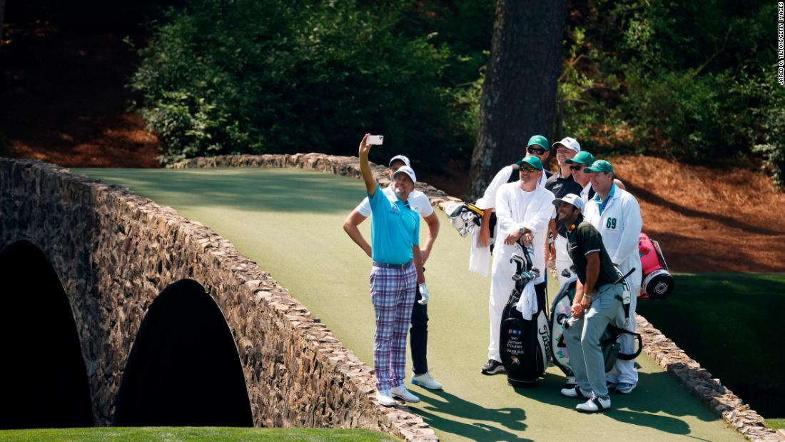 During a practice round on Wednesday, Ian Poulter takes a Hogan Bridge selfie with his playing partners and their caddies.