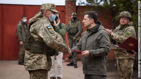 Ukrainian President Volodymyr Zelensky (right) shakes hands with a soldier during his visit to a front in Donbass, Ukraine, on April 08.