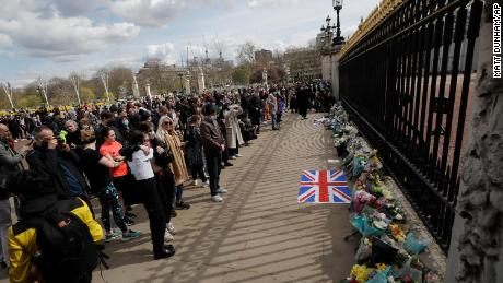 Mourners lay flowers and gather in front of Buckingham Palace.