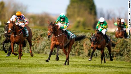 Blackmore riding Minella Times (middle) clears the last hurdle to win the Grand National.
