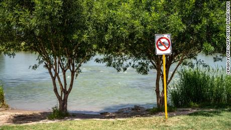 """This file photo from 2019 shows a """"No Swimming"""" sign near the Rio Grande in Piedras Negras, Mexico. The mother we met told us her family was on the banks of the river in Piedras Negras when they decided to separate."""