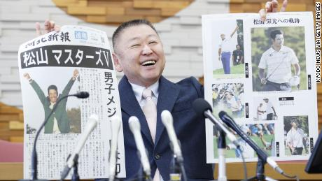Yasuhiko Abe, who coached golfer Hideki Matsuyama during his Tohoku Fukushi University years, holds special editions of newspapers featuring Matsuyama's Masters victory.