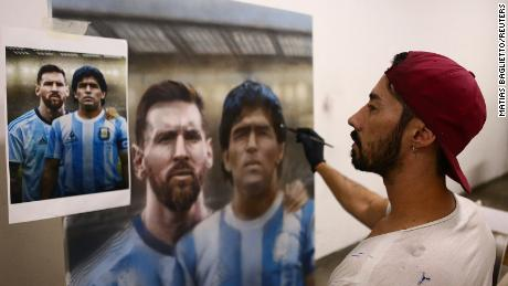 Artist Maximiliano Bagnasco shows off his painting of Diego Maradona.