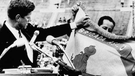 "President Kennedy displays the combat flag of the Cuban landing brigade, and declares to an audience of 40,000 that it ""will be returned this brigade in a free Havana."" The brigade was quickly stopped by Castro's army during the Bay of Pigs invasion."
