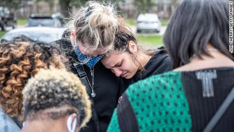 Mourners cry while gathering for a prayer vigil at Olivet Missionary Baptist Church on April 17, 2021, in Indianapolis in the wake of a mass shooting at a FedEx Ground Facility that left at least eight people dead.