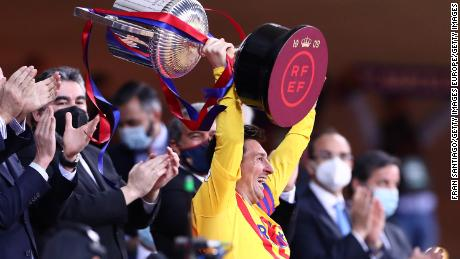 Lionel Messi hoists the Copa del Rey trophy aloft.