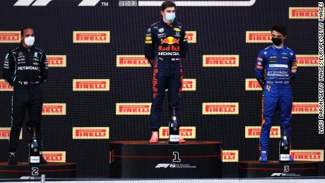 Lewis Hamilton, Max Verstappen and Lando Norris stand on the podium.