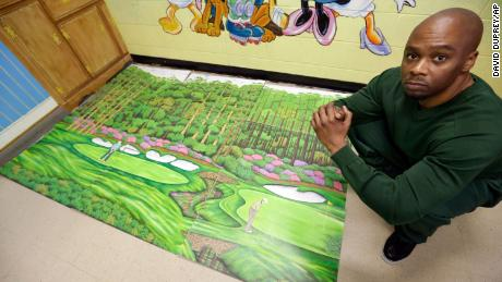 Dixon, an inmate at Attica Correctional Facility, poses with his golf art he created in prison.
