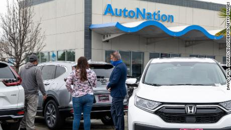 Customers look at cars for sale at an AutoNation dealership in Fremont, California. The company reported record first quarter profits Tuesday that were triple its year-ago earnings.