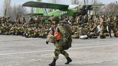 A Russian paratrooper walks near a plane during maneuvers in Taganrog, Russia, on Thursday, April 22, 2021.