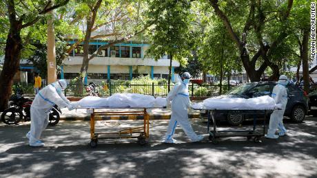 Balandžio 24 d. Sveikatos priežiūros darbuotojai, nešiojantys asmenines apsaugos priemones, nešiojo žmonių, kenčiančių nuo Covid-19, kūnus prie Guru Teg Bahadur ligoninės Naujajame Delyje (Indija).