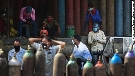 People wait to refill their medical oxygen cylinders for Covid-19 patients at an oxygen refilling station in Allahabad in April.