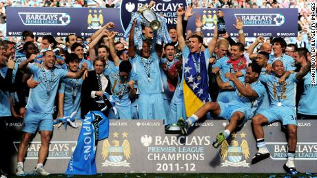 Manchester City players celebrate with the trophy following the Premier League victory in 2011.