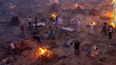 People wait to cremate bodies at a crematorium ground in New Delhi on April 23.