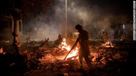 Workers can be seen at a crematorium where multiple funeral pyres are burning for people who lost their lives to Covid-19 on Thursday in New Delhi, India.
