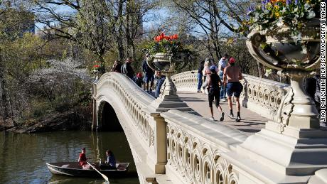 People stand on the Bow Bridge at Central Park on April 13 in New York City. The city is targeting a July 1 reopening.