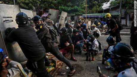 Protesters take cover behind homemade shields as they confront the police during a crackdown on demonstrations against the military coup in Yangon on March 16.