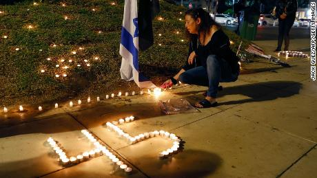 People light candles during a vigil in Habima Square in the Israeli coastal city of Tel Aviv on May 1, 2021.