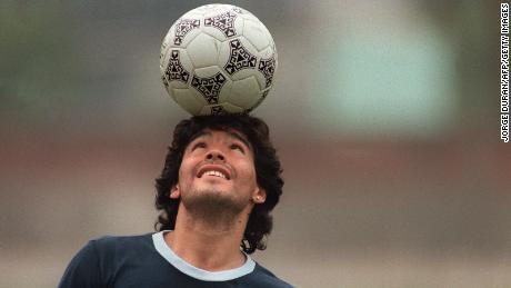 Argentine soccer star Diego Maradona, wearing a diamond earring, balances a soccer ball on his head as he walks off the practice field following the national selection's May 22, 1986 practice session in Mexico City.