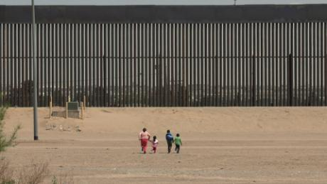 A woman and three young children race toward the wall at the US-Mexico border in Ciudad Juárez, Mexico. They were detained by US Border Patrol a few minutes later.