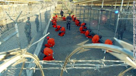 Detainees wearing orange jumpsuits are seen under guard on January 11, 2002 in a holding area at Camp X-Ray, on the US Naval Base at Guantanamo Bay, Cuba.