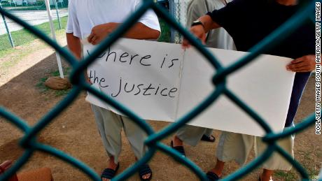 Uyghur detainees at Guantanamo Bay hold a sign calling for their release during a visit by reporters in 2009.