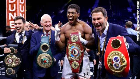 Anthony Joshua poses for a photo with the IBF, WBA, WBO & IBO World Heavyweight Title belts with Eddie Hearn and Barry Hearn after bout against Andy Ruiz Jr. at the Diriyah Season on December 07, 2019 in Diriyah, Saudi Arabia.