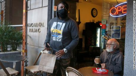 DoorDash driver Gleyson Coelho picks up an order for delivery in San Francisco on November 4, 2020. Many frontline workers have been hailed as heroes during the pandemic.