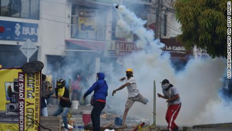 3 مئی 2021 کو کولمبیا کے شہر کیلی میں ایک مظاہرین نے ہنگامہ آرائی کرنے والے پولیس افسروں پر آنسو گیس کا ڈبہ پھینک دیا۔