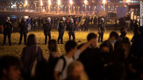 بارسلونا میں لوگ ساحل سمندر پر باندھتے ہی پولیس اہلکار پہرہ دیتے ہیں۔