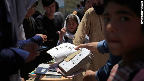 Afghans go through belongings left behind after the blasts on Saturday.