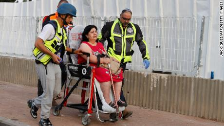 Israeli rescue teams evacuate a woman from a residential neighborhood in Ashkelon Tuesday after rockets were fired from the Gaza Strip towards Israel overnight amid spiralling violence.