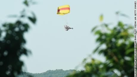 A staff member uses a powered parachute to search for an escaped leopard in the mountains near Hejia Village in the West Lake District of Hangzhou, capital of east China's Zhejiang Province, May 9, 2021.
