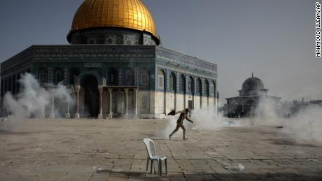 A Palestinian man runs from tear gas during clashes with Israeli security forces at the Al Aqsa Mosque.