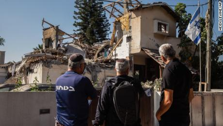 People look at a house Wednesday in Yehud, central Israel, after it was hit by a rocket fired from the Gaza Strip.