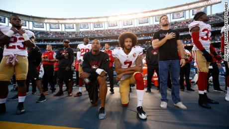 Eric Reid and Kaepernick kneel on the sideline during the national anthem.
