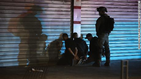 An Israeli security soldier detains three Arabs during clashes between Jews, Arabs and police in Lod on May 13.