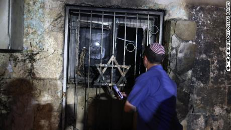 An Israeli man looks inside a synagogue after it was set on fire by Arab-Israelis in the city of Lod, Israel, on May 14.