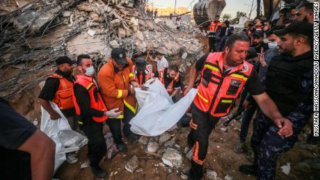 Palestinian civil defense teams take part in recovery efforts amid the rubble of a building after Israeli fighter jets conducted airstrikes in Beit Lahia, Gaza on May 13.