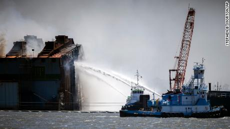 Firefighters working off two tug boats hose down the remains of the overturned cargo ship.
