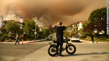 A man takes a photo of the plume of smoke created by the Palisades fire in Topanga State Park, North West of Los Angeles on May 15, 2021.