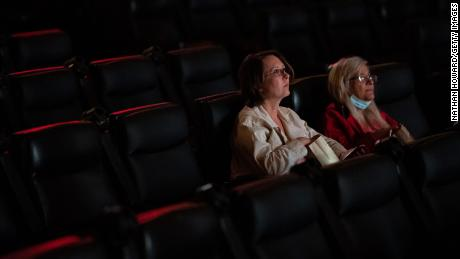 Two moviegoers attend a nearly empty film showing at the Kiggins Theatre on May 14 in Vancouver, Washington. Gov. Jay Inslee announced Thursday the statewide mask mandate would no longer apply to fully vaccinated adults.
